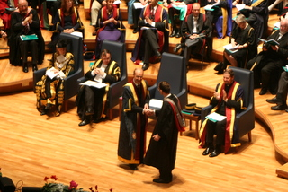 Tim receives his degree at his graduation ceremony