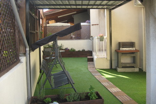 transformed side yard, with barbecue and artificial grass